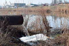 Ein großes Rohr, von dem Abwasser in den Fluss fließt Lizenzfreies Stockfoto