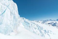 Ein großes schneebedecktes Gletscherhoch in den Bergen vor dem hintergrund des Kaukasus und des blauen Himmels Lizenzfreie Stockfotos