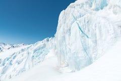 Ein großes schneebedecktes Gletscherhoch in den Bergen vor dem hintergrund des Kaukasus und des blauen Himmels Stockfoto