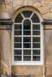 Ein großes traditionelles gewölbtes Fenster in einer Sandbacksteinmauer lizenzfreie stockfotos