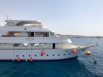 Ein großes weißes dreistöckiges Boot, ein Schiff, ein Kreuzfahrtschiff mit Lebenbojen, Öffnungen auf einem tropischen warmen südl lizenzfreie stockbilder