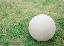 Ein großer Zement-Ball, der auf einem grasartigen Gebiet stillsteht lizenzfreies stockfoto