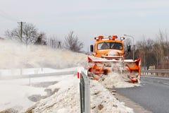Ein großes Auto mit einem Pflug klärt die Straße vom Schnee Spezielle Ausrüstung der orange Fracht kämpft mit den Elementen im Wi lizenzfreie stockbilder
