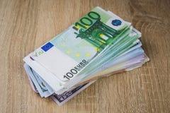 ein gro?es Pack von Bargeldrechnungs-Dollar-Eurorubeln in den S?tzen auf einer Tabelle von strukturierten Brettern stockbilder