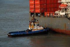 Ein großes Containerschiff, das leicht zu einem Dock am Cartagena-Hafen gedrückt wird Stockfotografie