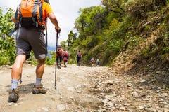 Ein Gruppe von Personenen-Trekking auf Schotterweg in Nepal lizenzfreie stockfotografie