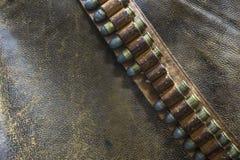 Ein Gunbelt mit Kugeln auf einem abgenutzten ledernen Hintergrund Lizenzfreie Stockbilder