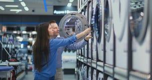 Ein gut aussehender Mann und eine Frau eine Waschmaschine beschließen, um offen die Tür zu kaufen und die Beschichtung der Trom stock video footage