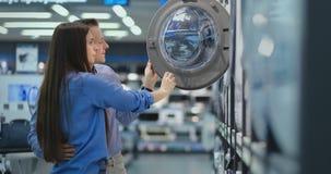 Ein gut aussehender Mann und eine Frau eine Waschmaschine beschließen, um offen die Tür zu kaufen und die Beschichtung der Trom stock footage