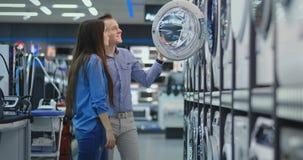 Ein gut aussehender Mann und eine Frau eine Waschmaschine beschließen, um offen die Tür zu kaufen und die Beschichtung der Trom stock video