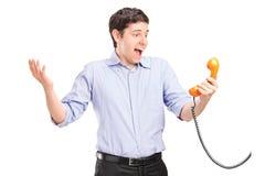 Ein gutaussehender Mann, der ein Retro Telefon und ein Gestikulieren hält Stockbild