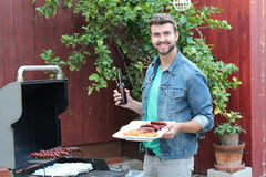 Ein gutaussehender Mann, der Huhn kochen und Würste auf dem Grill grillen Lizenzfreie Stockfotos