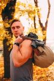 Ein gutaussehender Mann steht in einem Herbstpark in der Sportkleidung stockfotografie