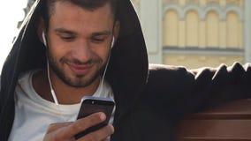 Ein guter Junge reagiert auf Mitteilungen im Telefon stock footage