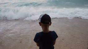 Ein guter kleiner Kerl kleidete in der dunklen Kleidung und eine Kappe, Stand auf der Seeseite und Blicke in dem turbulenten adri stock footage