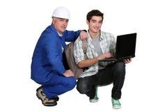 Ein Händler, der seinem Lehrling hilft stockfotos