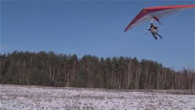 Ein Hängegleiter landet auf einer schneebedeckten Wiese stock video footage