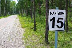 Ein Höchstgeschwindigkeitszeichen des Maximums 15 entlang einer Schotterstraße stockbilder