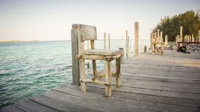 Ein hölzerner alter verwitterter Stuhl auf kleinem Hafen mit Seehintergrundlandschaft Indonesien lizenzfreies stockfoto