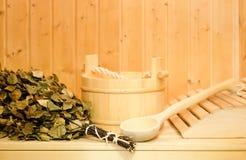 Ein hölzerner Eimer, ein Birkenbesen und andere Zusätze in einer finnischen klassischen Sauna oder in einem russischen Bad Freier stockfoto