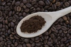 Ein hölzerner Löffel mit gemahlenem Kaffee und Kaffeebohnen lizenzfreie stockbilder