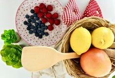Ein hölzerner Löffel, Zitronen, Orangen und Himbeeren lizenzfreie stockfotografie
