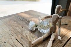 Ein hölzerner Mann sitzt und setzte den Arm auf das Glas des Wassers Stockfotos