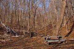 Ein hölzerner Picknicktisch teilweise bedeckt im Schnee nahe bei einer Holzbrücke im Winterholz stockfoto