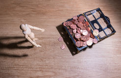 Ein hölzerner Puppenmann mit seinen Einsparungen, Goldmünze Alle verfassten (sentence mit Cent fünfundzwanzig Cent, fünfzig des t Stockfoto