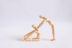 Ein hölzerner Puppenmann trainiert mit seinem Freund lizenzfreies stockfoto