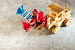 Ein hölzerner Spielzeugtraktor trägt Weihnachtsspielwaren in Form von multi Lizenzfreie Stockfotografie