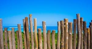 Ein hölzerner Stock als Zaun mit schönem Meer und grüner Baum auf karimun jawa Insel lizenzfreie stockfotografie