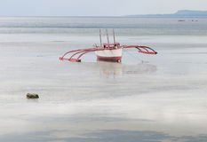 Ein hölzernes Boot auf dem Meer in Bangbao, Philippinen Stockbild