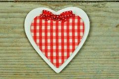 Ein hölzernes Herz auf einem hölzernen Hintergrund Stockbilder
