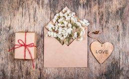 Ein hölzernes Herz, ein Buchstabe mit Blumen und ein Geschenk St Valentinsgruß ` s Tag Stockfotos
