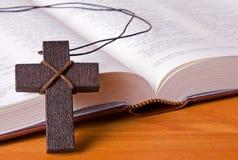 Ein hölzernes Kreuz, das gegen eine Bibel stillsteht Lizenzfreie Stockfotos