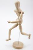Ein hölzernes Mannequin, das uns laufen lässt und betrachtet Stockfotos