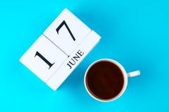 Ein hölzernes Notizbuch mit einem Datum am 17. Juni und eine Kaffeetasse auf einem blauen Pastellhintergrund Vater und Sohn Stockfoto