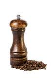 Ein hölzernes peppermill mit Pfefferkörnern auf weißem Hintergrund Stockfotografie