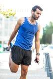 Ein hübscher Athlet, der sein Bein ausdehnt lizenzfreie stockfotografie
