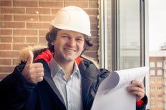 Ein hübscher Bauarbeiter, der ein Daumen-obenzeichen gibt Authentischer Bauarbeiter auf tatsächlicher Baustelle weich Stockfoto