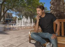 Ein hübscher geeigneter Mann sitzt auf einer Bank am Stadtpark durch den Wasserbrunnen lizenzfreie stockfotografie