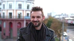 Ein hübscher grober Mann mit einem Bart, der Kamera, Winks, freundlich lächelnd in der Stadt untersucht Langsames MO stock video footage