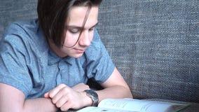 Ein hübscher Junge ein Jugendlicher liest ein Buch auf einem grauen Sofa, braune Augen Lizenzfreies Stockfoto