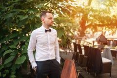 Ein hübscher junger Geschäftsmann in einem weißen Hemd und binden einen Schmetterling an einem Geschäftsabendessen stockfotografie