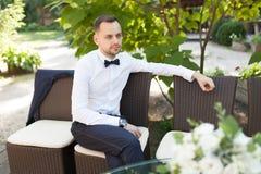 Ein hübscher junger Geschäftsmann in einem weißen Hemd und binden einen Schmetterling an einem Geschäftsabendessen lizenzfreies stockbild