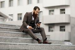 Ein hübscher junger Geschäftsmann unter Verwendung seines Telefons, während auf den Schritten sitzt Stockfotos