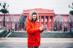 Ein hübscher junger Kerl mit Bart und roter Jacke in der Haube ein Student benutzt einen Handy, schreibt, schreibt eine Korrespon stockbild