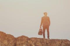 Ein hübscher junger Mann untersucht den Abstand auf den Felsen Stockfotografie