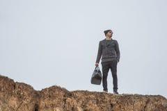 Ein hübscher junger Mann untersucht den Abstand auf den Felsen Lizenzfreie Stockbilder